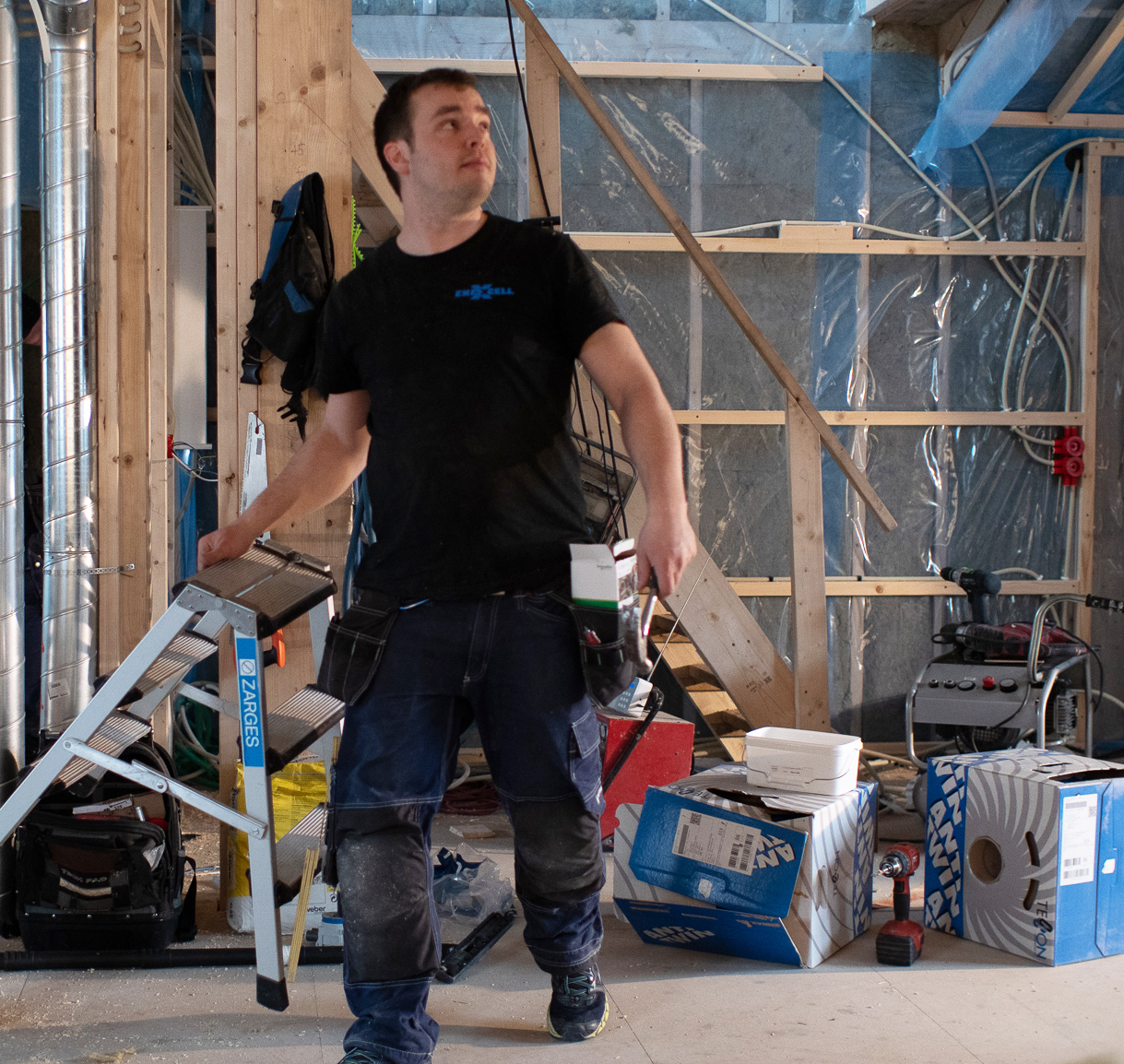 Elektriker på byggeplass dom bærer verktøy og stige
